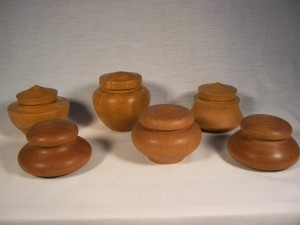 A collection of lidded boxes in light mahogany